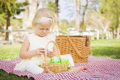 Cute Baby Girl Enjoying Her Easter Eggs on Picnic Blanket Stock Photos