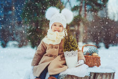 Cute baby girl enjoying winter walk in snowy park, wearing warm hat Stock Photo