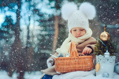 Cute baby girl enjoying winter walk in snowy park, wearing warm hat. And coat Stock Photography