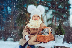 Cute baby girl enjoying winter walk in snowy park, wearing warm hat. And coat Stock Photos
