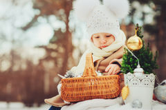 Cute baby girl enjoying winter walk in snowy park, wearing warm hat. And coat Stock Photo