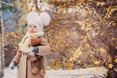 Cute baby girl enjoying winter walk in snowy park, wearing warm hat. And coat Stock Images