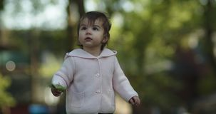 Cute baby girl exploring a park in late spring.