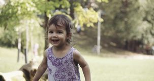 Cute baby girl exploring a park in late summer and jumping for joy.