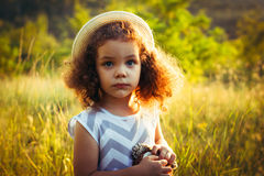 Cute curly baby girl in summer or fall time. Toddler sweet girl in a dress with zigzag print in a park or forest. She wear a hat stock image