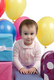 Cute baby girl with gifts and balloons Royalty Free Stock Photos