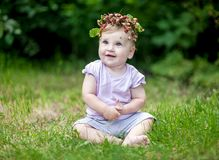 Cute baby girl with gold hair and wild strawberry crown royalty free stock images