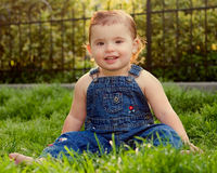 Cute baby girl on grass. Cute baby girl sat on grass in denim overalls or dungarees stock photography
