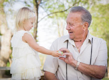 Cute Baby Girl Handing Easter Egg to Grandfather Outside Stock Images