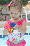 Cute baby girl is having fun in the pool Stock Photos