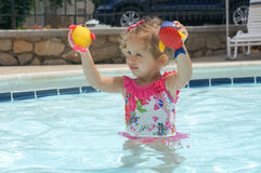 Cute baby girl is having fun in the pool Stock Image