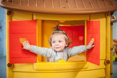 Cute baby girl head out of plastic window Royalty Free Stock Photography