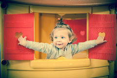 Cute baby girl head out of plastic window. Cute baby girl head out of red plastic window Royalty Free Stock Images