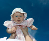Cute baby girl held in air stock photography