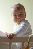Cute baby girl in her cot Stock Images