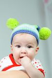 Baby girl and her funny hat fingers in her mouth. Cute baby girl and her funny hat, fingers in her mouth Royalty Free Stock Photos