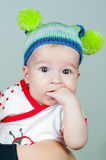 Baby girl and her funny hat fingers in her mouth Royalty Free Stock Photos