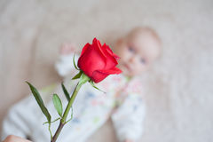 Cute baby girl holding a bouquet of flowers rose Stock Image