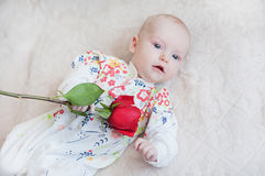 Cute baby girl holding a bouquet of flowers rose Stock Photos