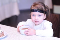 Cute baby girl holding cup of black tea in cafe Stock Photos