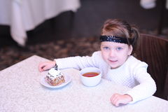 Cute baby girl holding cup of black tea in cafe Stock Image