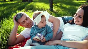 Cute baby girl holding her shoe and parents lying next to her on grass in park