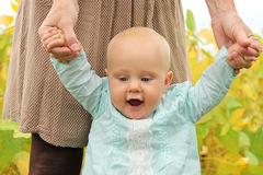 Cute Baby Girl Holding Mothers Hands Walking Stock Images