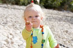 Cute baby girl holding out a pebble Royalty Free Stock Photos