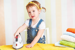 Cute  baby girl housewife iron clothes iron, is engaged in domes Royalty Free Stock Image