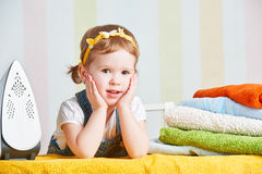 Cute  baby girl housewife iron clothes iron, is engaged in domes Royalty Free Stock Photography