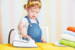 Cute  baby girl housewife iron clothes iron, is engaged in domes Stock Images
