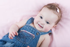 Cute baby girl in a jeans dress on a pink blanket Stock Photography