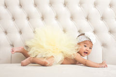 Cute baby girl laying on a couch Stock Images