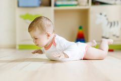 Cute baby girl learning crawling and sitting in children room. At home. New born child, little girl lying on belly. Family, new life, childhood, beginning royalty free stock photos