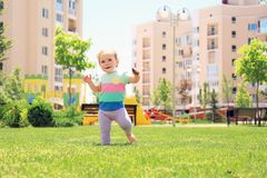 Cute baby girl learning to walk outdoors. On sunny day stock photo