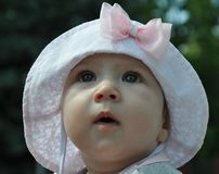 Cute baby girl in a light pink hat with a bow wondering the sky royalty free stock photos