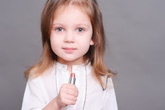 Cute baby girl with lipstick Stock Photos