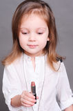 Cute baby girl with lipstick Stock Images