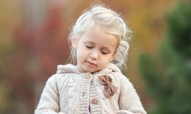 Cute baby girl looking thoughtfully down on a colorful background. Close-up stock images