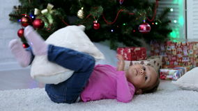 Cute baby girl lying on the back under christmas tree and playing with pillow stock video footage