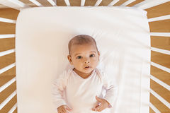 Cute Baby Girl Lying in the Crib. At home Stock Image