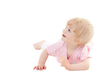 Cute baby girl lying on the floor and looks up royalty free stock photography