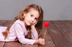 Cute baby girl lying on floor with valentines heart Royalty Free Stock Photos