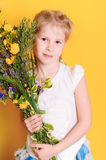 Cute baby girl with meadow flowers. Cute little girl holding meadow flowers on yellow background Stock Photography