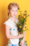 Cute baby girl with meadow flowers. Cute little girl holding meadow flowers on yellow background Royalty Free Stock Photo