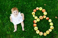 Cute baby girl with number 8 as eight months made with ripe apples on a farm in early autumn. Little baby girl playing royalty free stock photography