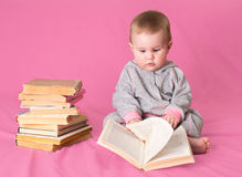 Cute baby girl with old books reading on pink background. Forwar Stock Image