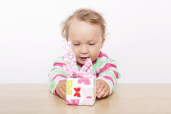 Cute baby girl opening present. Stock Photography
