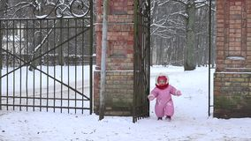 Cute baby girl in overall walk through snowy retro park gate in winter. 4K stock footage