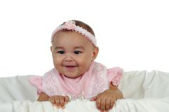Cute Baby Girl in Pink. Closeup portrait of an adorable smiling girl wearing a pink dress in a crib stock photography